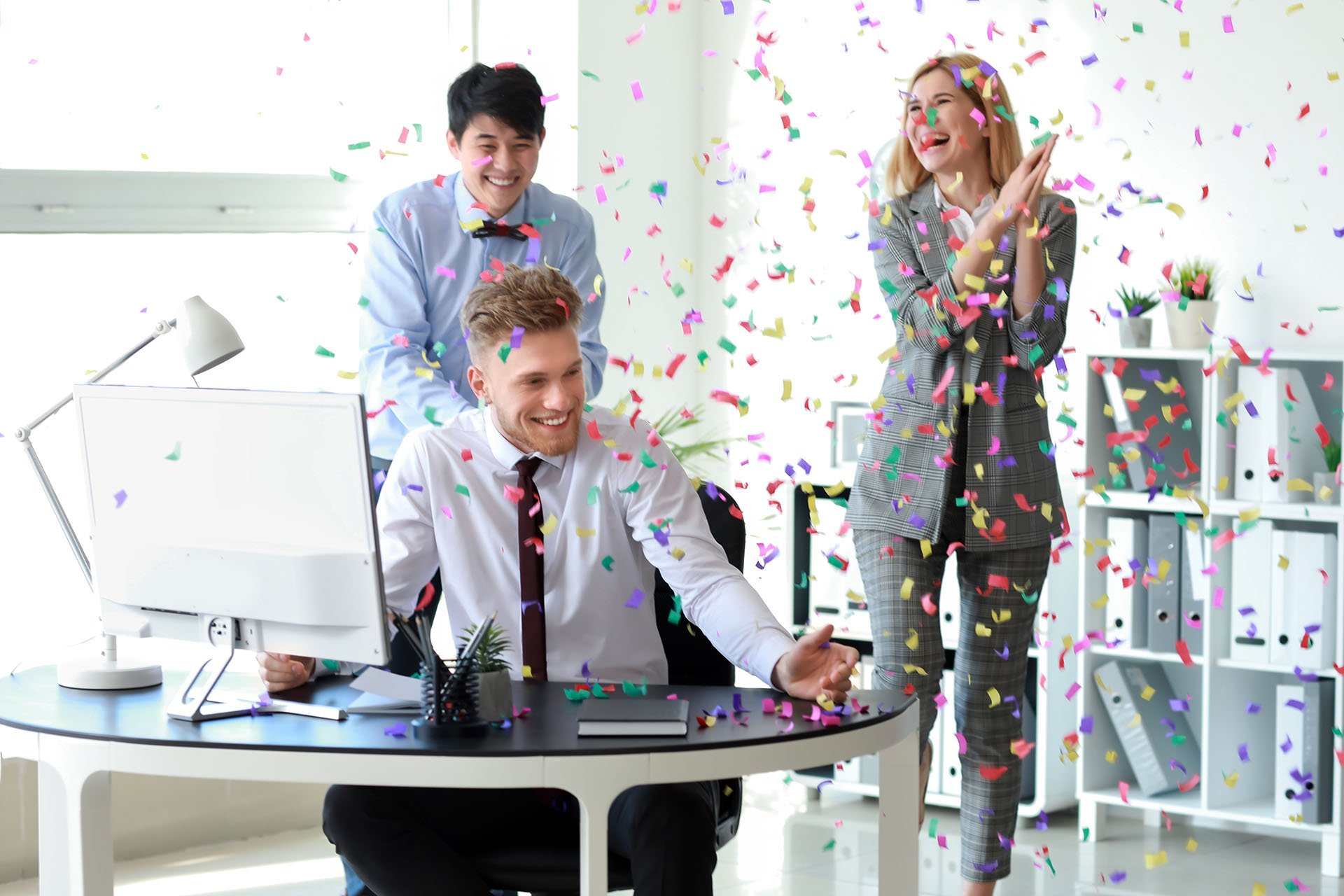 Two men and a woman are showered with confetti at a new employee's desk