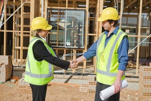 A man and woman at a construction site shake hands